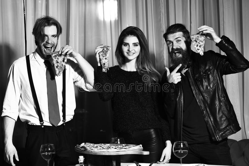 Happy friends eating tasty pizza slices with thumbs up gestures. Happy friends, pretty girl and two bearded men, hipsters with beards, eating tasty pizza slices royalty free stock photos