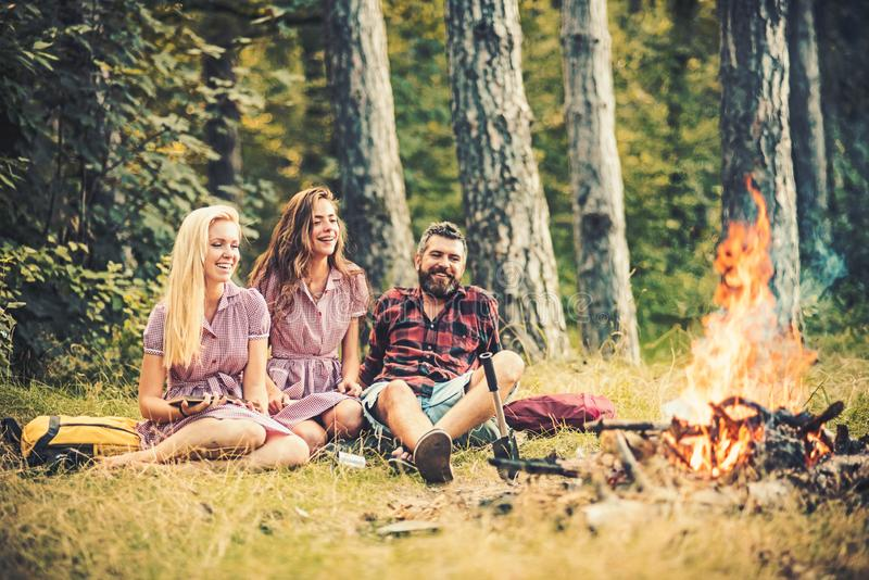 Happy friends enjoying evening outdoors. Young man and two women sitting around campfire. Friends camping in wilderness royalty free stock photo