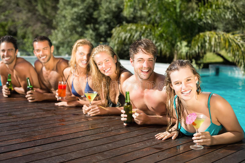 Happy friends enjoying at the swimming pool stock photos