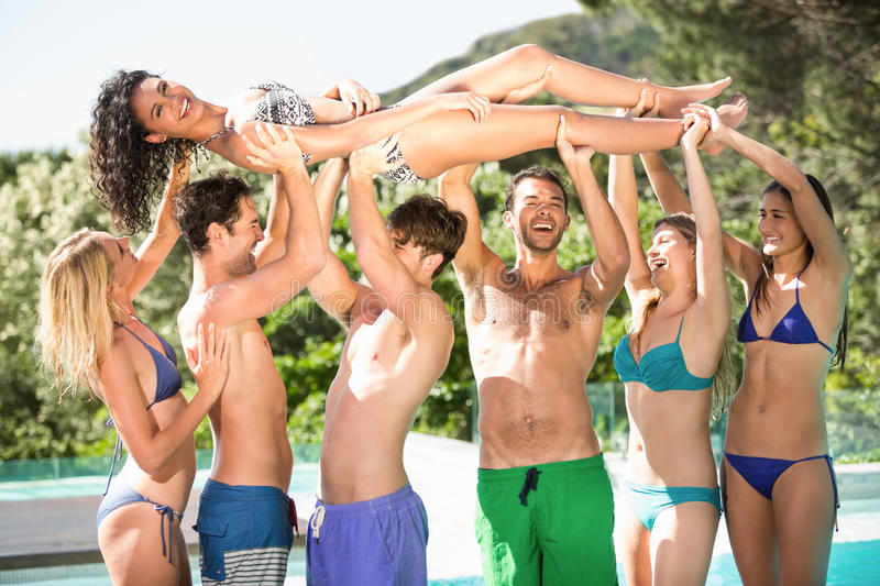 Happy friends enjoying at the swimming pool stock photo