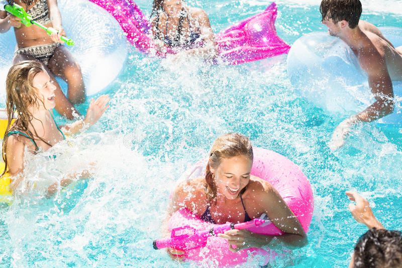 Happy friends enjoying in the swimming pool stock photo