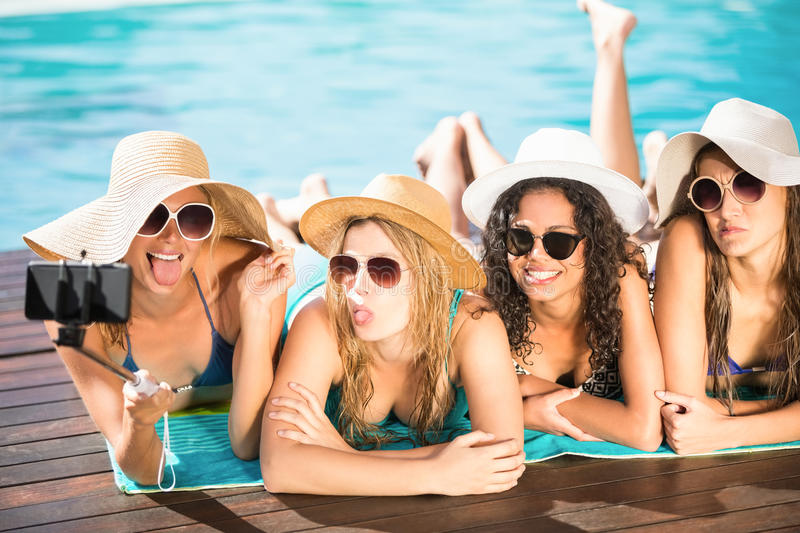 Happy friends enjoying at the swimming pool stock image