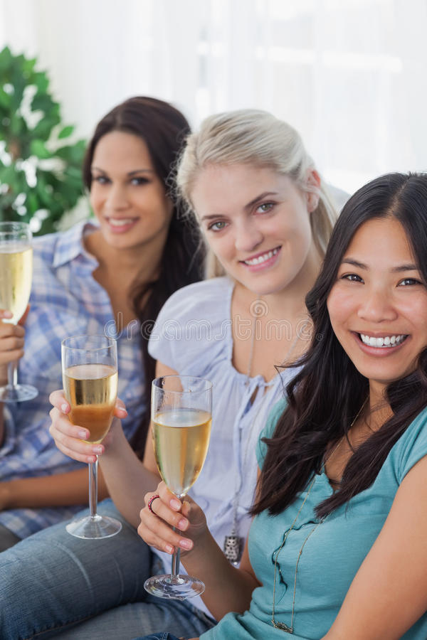Happy friends enjoying white wine together looking at camera stock photos