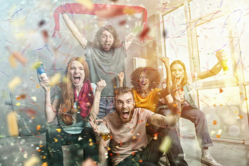 Happy friends of football fans watching soccer on tv and celebrating victory with falling confetti. royalty free stock photos