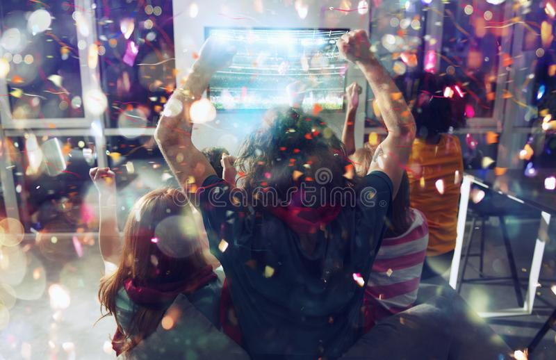 Happy friends of football fans watching soccer on tv and celebrating victory with falling confetti. Friendship, sports and entertainment concept stock photo