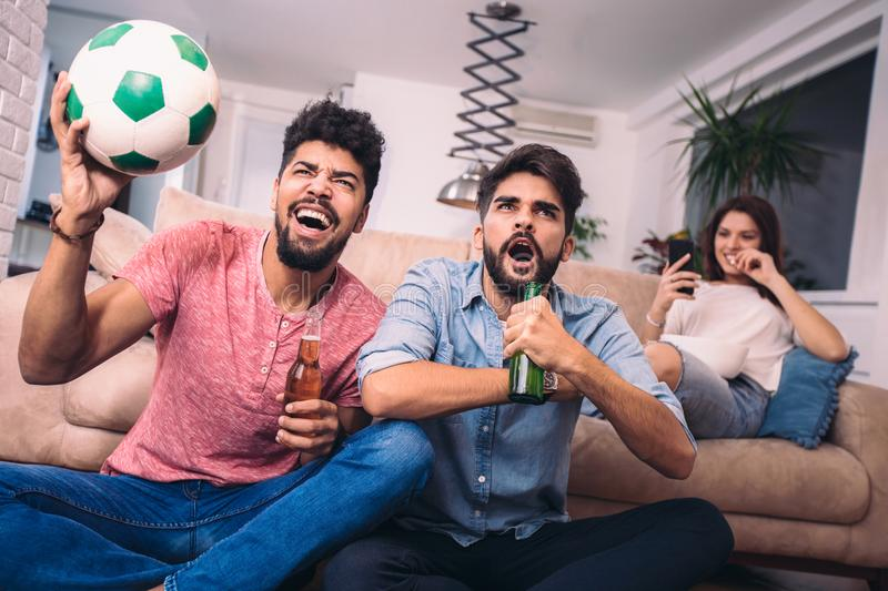 Happy friends or football fans watching soccer on tv. And celebrating victory at home.Friendship, sports and entertainment concept royalty free stock image