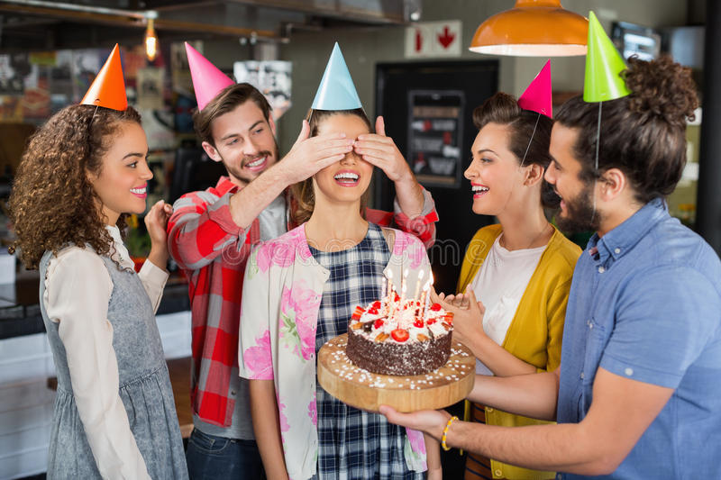 Happy friends giving suprise to woman during her birthday. Happy friends with cake giving suprise to woman during her birthday royalty free stock photography