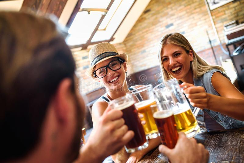 Happy friends having fun at bar - Young trendy people drinking beer and laughing together royalty free stock images