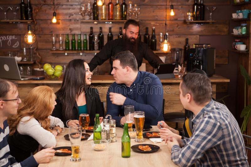 Happy friends group drinking beer and eating pizza at bar restaurant . royalty free stock image