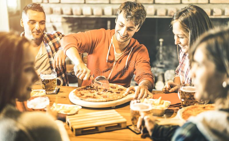 Happy friends group eating pizza at chalet bar restaurant royalty free stock image