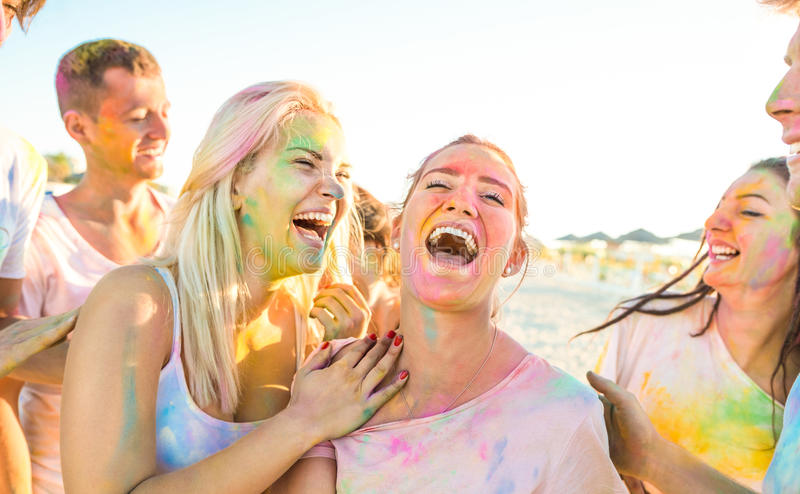 Happy friends group having fun at beach party on holi festival. Summer vacation - Young people laughing together with genuine carefree mood royalty free stock photos