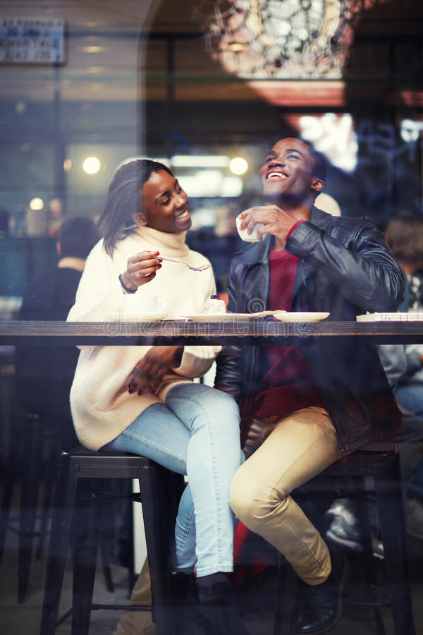 happy friends having coffee together, laughing young couple in cafe stock images