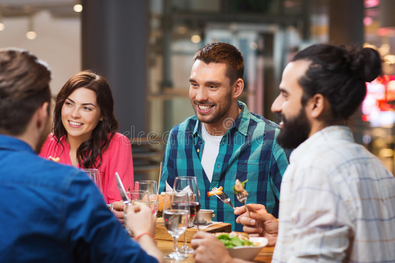 Happy friends having dinner at restaurant royalty free stock photos