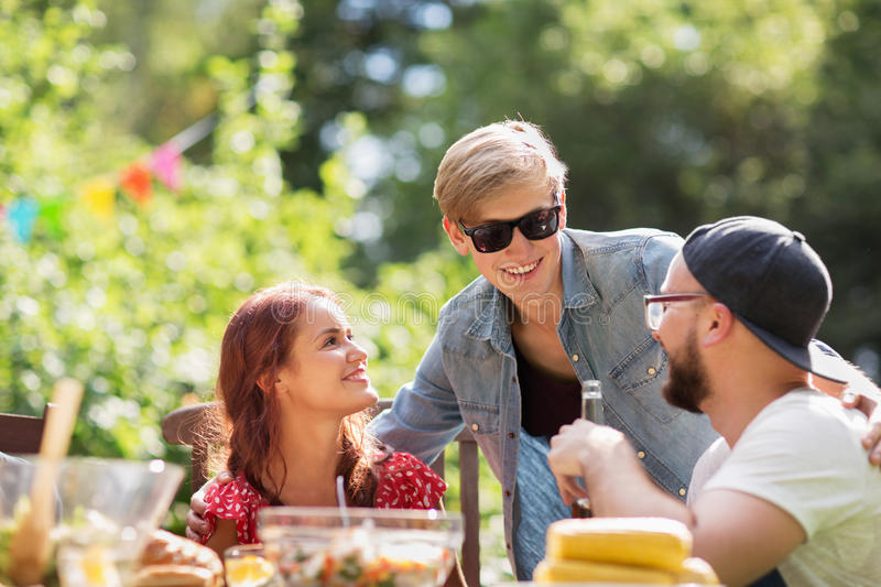 Happy friends having dinner at summer garden party. Leisure, holidays, communication, people and concept - happy friends having dinner at summer garden party royalty free stock photography