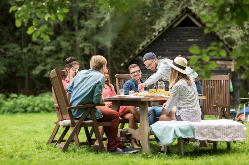 Happy friends having dinner at summer garden party stock images
