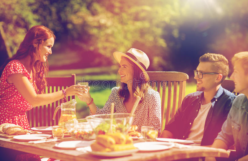 Happy friends having dinner at summer garden party. Leisure, holidays, eating, people and food concept - happy friends having dinner at summer garden party stock image