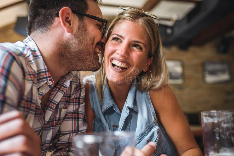 Happy friends having fun at bar - Young trendy couple drinking beer and laughing together royalty free stock photography