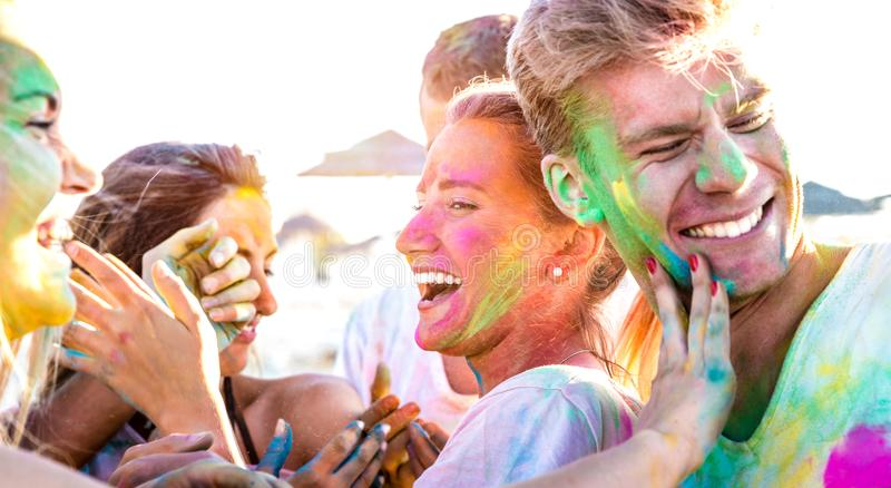 Happy friends having fun at beach party on holi colors festival event - Young people laughing together with candid excited mood royalty free stock photos