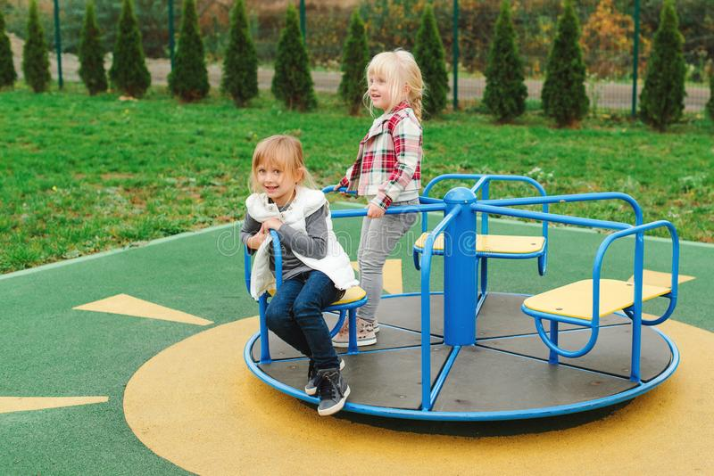 Happy friends having fun on carousel outdoors. Cute little girls enjoying at playground. Happy and healthy childhood. Modern royalty free stock photography