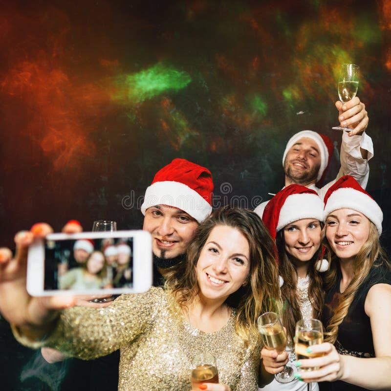 Happy friends having fun celebrating Christmas stock images