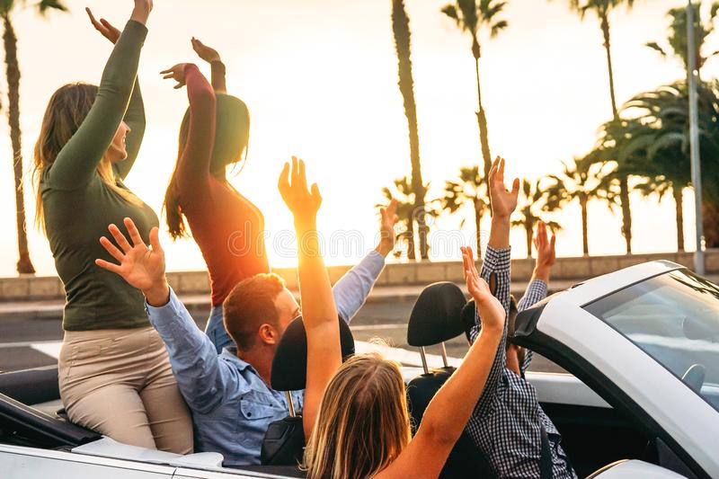 Happy friends having fun in convertible car in vacation - Young people enjoying time traveling and dancing in a cabrio auto royalty free stock photography
