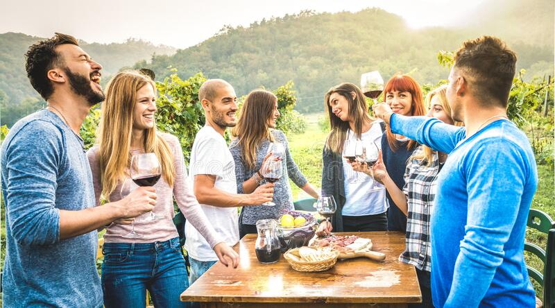 Happy friends having fun drinking red wine in vineyard - Milenial people enjoying harvest time together at countryside farm house stock photos