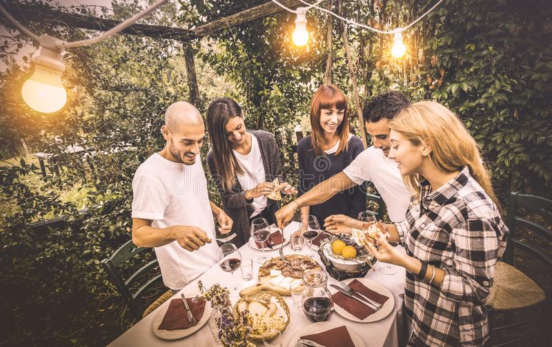 Happy friends having fun eating local food at garden picnic party stock photography