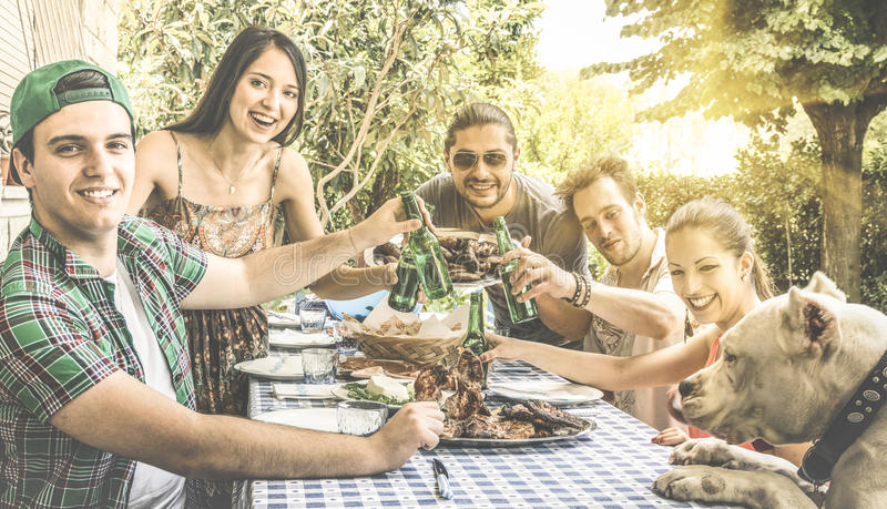 Happy friends having fun eating and toasting together at bbq. Happy friends having fun eating and toasting together at backyard garden barbecue - Friendship and royalty free stock image