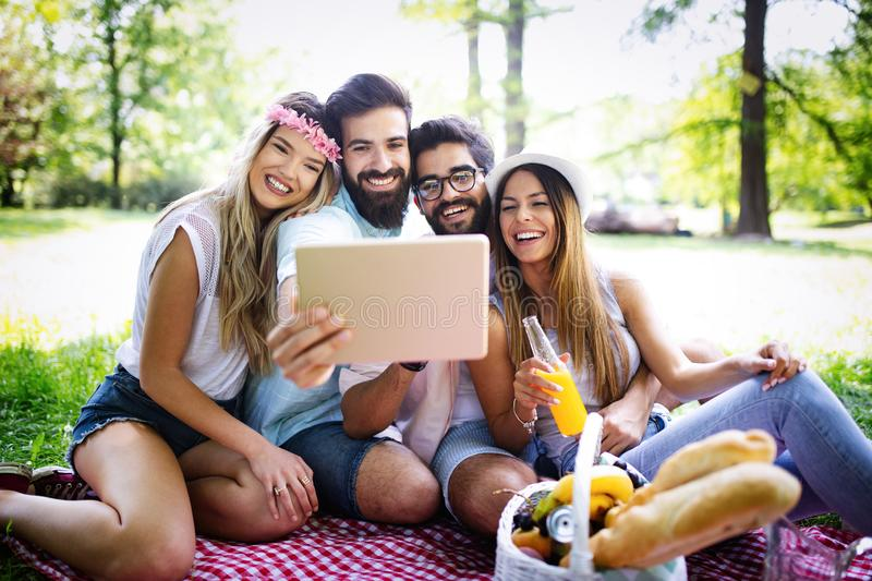 Happy young friends having fun outside in nature, taking selfie stock image
