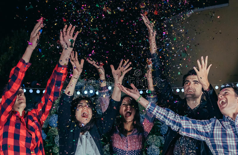 Happy friends having fun among the party confetti royalty free stock photography