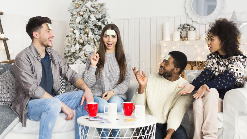 Happy friends having fun and playing game Who I Am stock photos