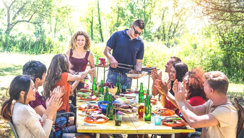 Happy friends having fun together at barbecue picnic party - Young people millenials at pic nic on open air festival royalty free stock images