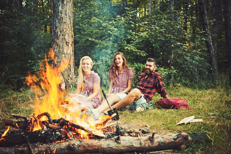 Happy friends having picnic in woods. Cheerful youngsters enjoying summer evening near campfire, weekend in countryside royalty free stock photos