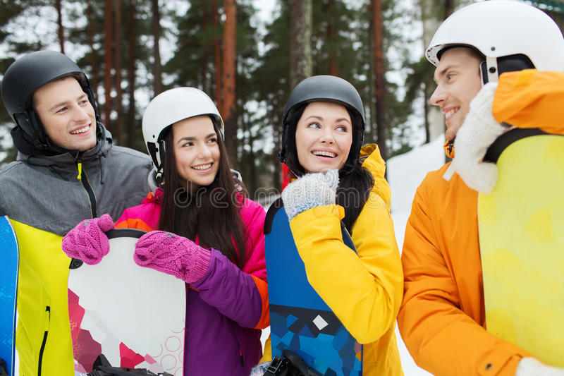 Happy friends in helmets with snowboards talking royalty free stock photos
