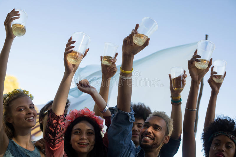 Happy friends holding beer glasses while enjoying music festival. Happy friends holding beer glasses with arms raised while enjoying music festival royalty free stock photos
