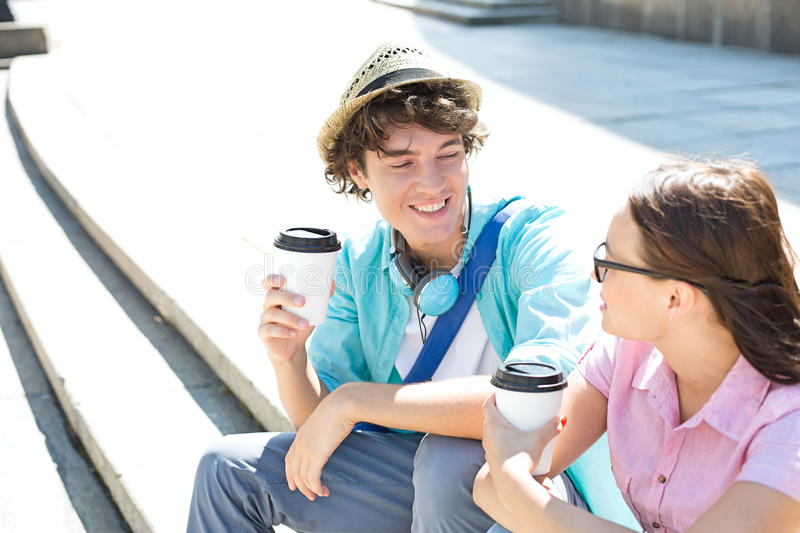 Happy friends holding disposable coffee cups while sitting on steps outdoors royalty free stock images
