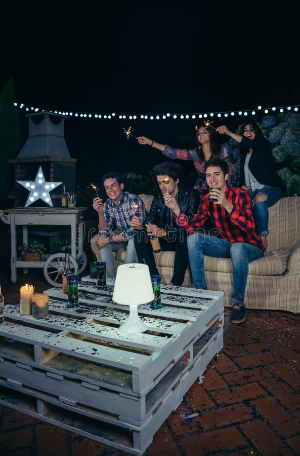 Happy friends holding sparklers in a night party stock images
