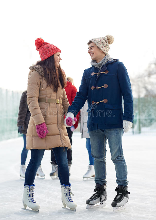 Happy friends ice skating on rink outdoors royalty free stock image