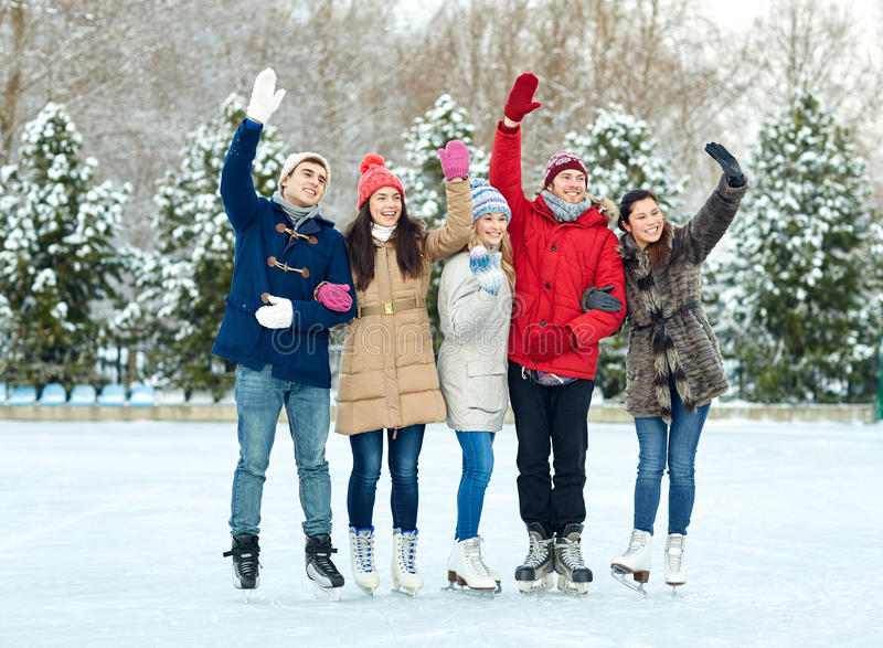 Happy friends ice skating on rink outdoors. People, winter, friendship, sport and leisure concept - happy friends ice skating and waving hands on rink outdoors royalty free stock photo