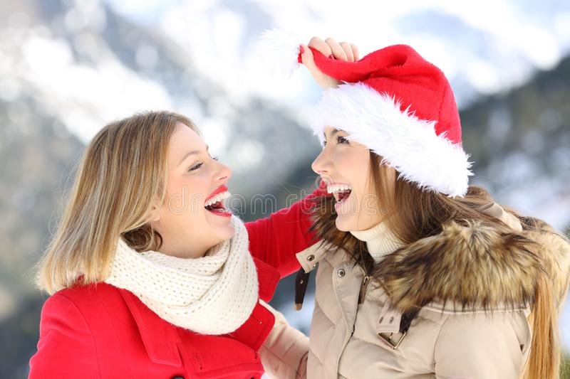 Happy friends joking on christmas holidays. Two happy friends joking on christmas holidays with a snowy mountain in the background royalty free stock photo