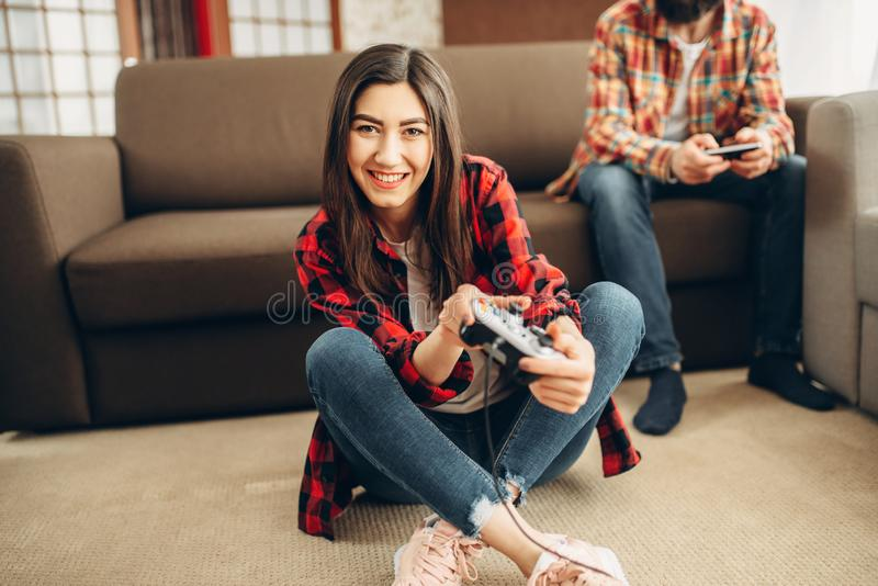 Happy friends with joysticks plays video console. At home. Group of gamers playing videogame, male and female players have a competition stock photo