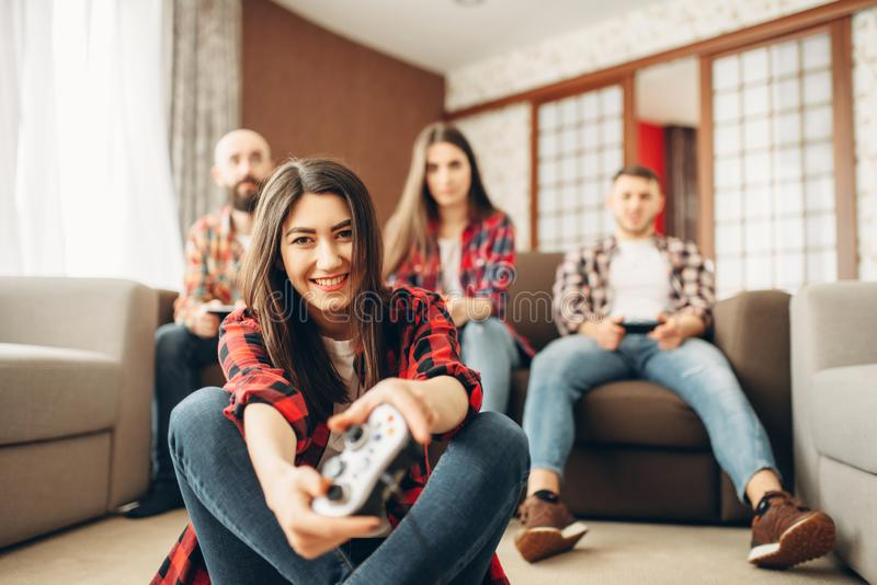 Happy friends with joysticks plays video console. At home. Group of gamers playing videogame, players have a competition stock photo