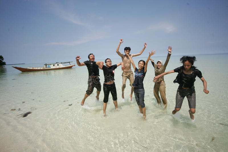 Happy friends jumping at the beautifull beach stock photo