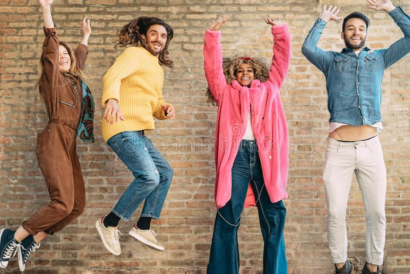 Happy friends jumping together outdoor - Millennial young people having fun dancing and celebrating outside stock photography