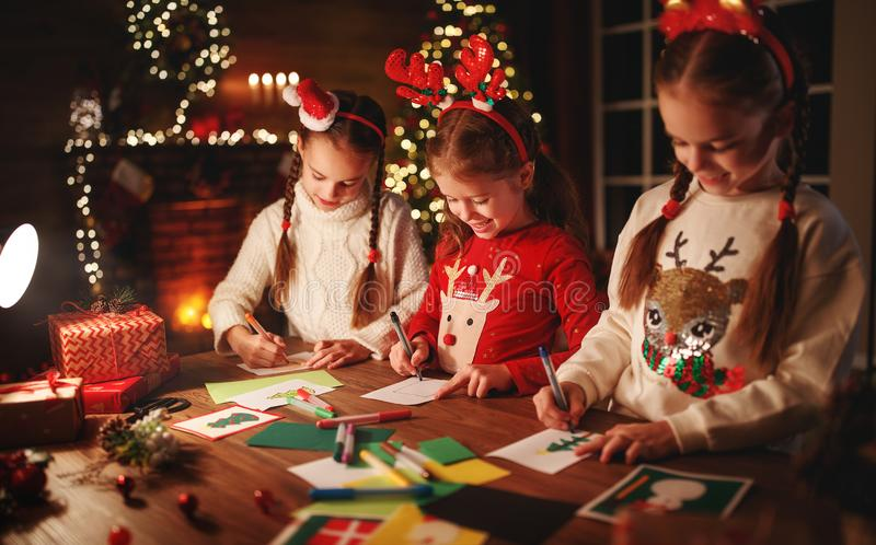 Happy friends kids draw decorations and write  letter to Santa near Christmas tree royalty free stock photo