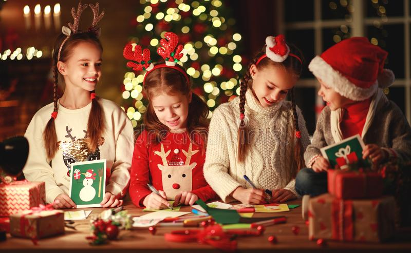 Happy friends kids draw decorations and write  letter to Santa near Christmas tree stock images