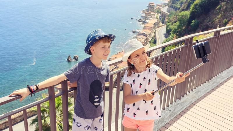 Happy friends kids taking selfie in beautiful town of Scilla Italy, smiling children having fun together sharing pictures online stock photography
