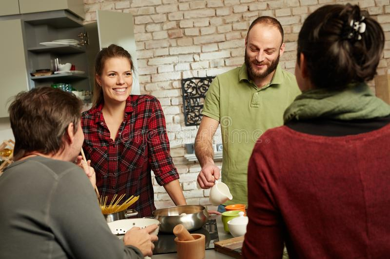 Happy friends in kitchen. Happy couple and friends talking and cooking together in kitchen royalty free stock photo