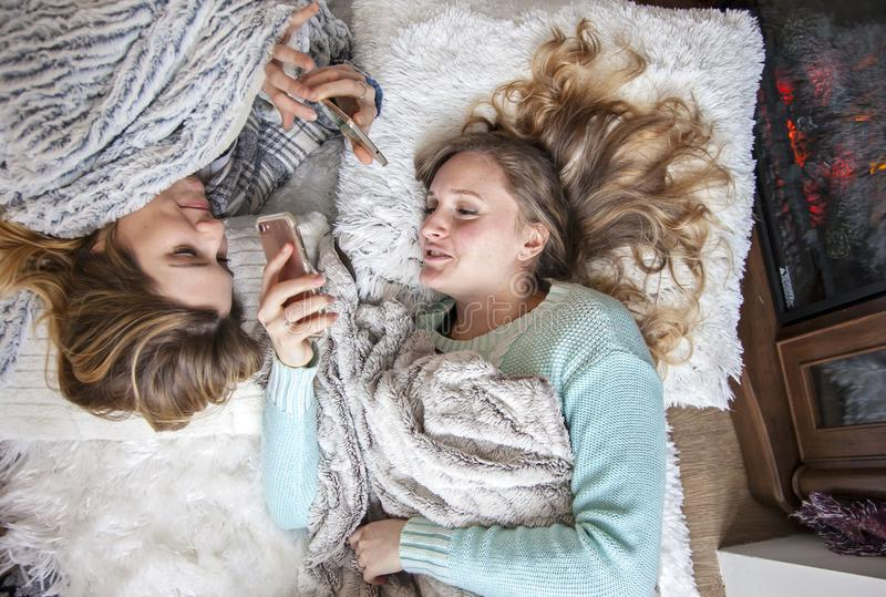 Happy friends laying on blankets with phones laughing. Two laughing young women on blankets chatting, gossiping, looking at phones. Girls weekend. sleepover royalty free stock photography