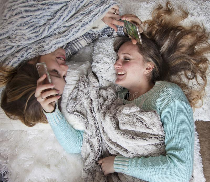 Happy friends laying on blankets with phones laughing. Two laughing young women on blankets chatting, gossiping, looking at phones. Girls weekend. sleepover royalty free stock image